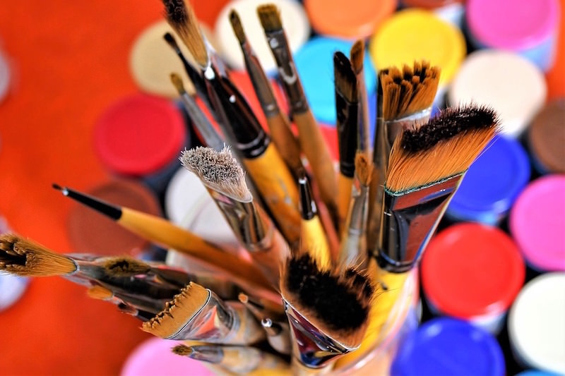 Brushes in the midst of acrylic paint bottles