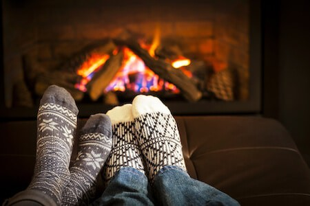 Feet warming by wood fireplace