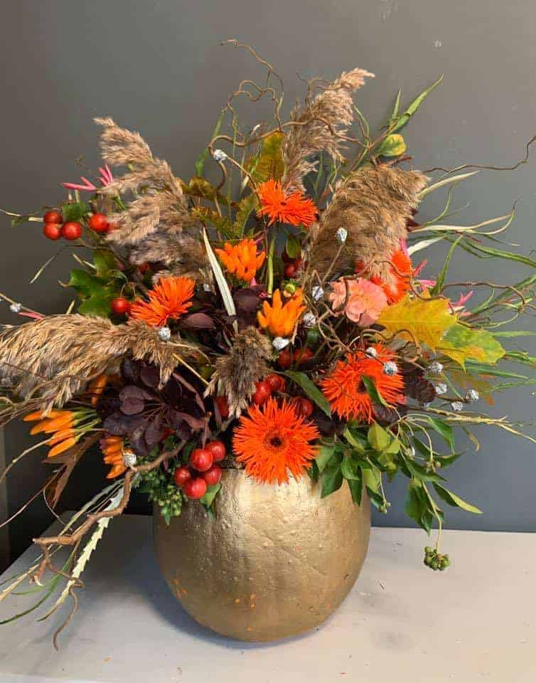 autumn flower arrangement idea gold pumpkin orange asters, grassesm rose hips, berries and ivy #autumn #flowers #pumpkin #gold #orange