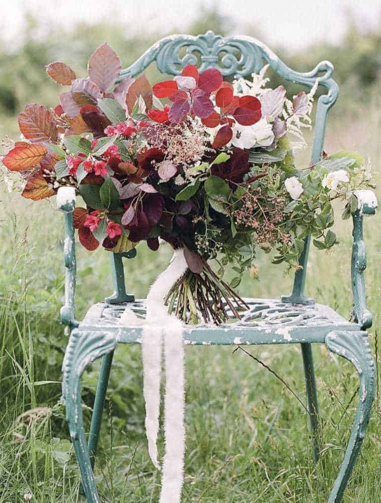 love this seasonal autumn flower arrangement on vintage metal chair using berries, autumn leaves, foraged greenery and flowers. #frombritainwithlove #mybritainwithlove #britishflowers #autumnflowerideas #autumnleaves