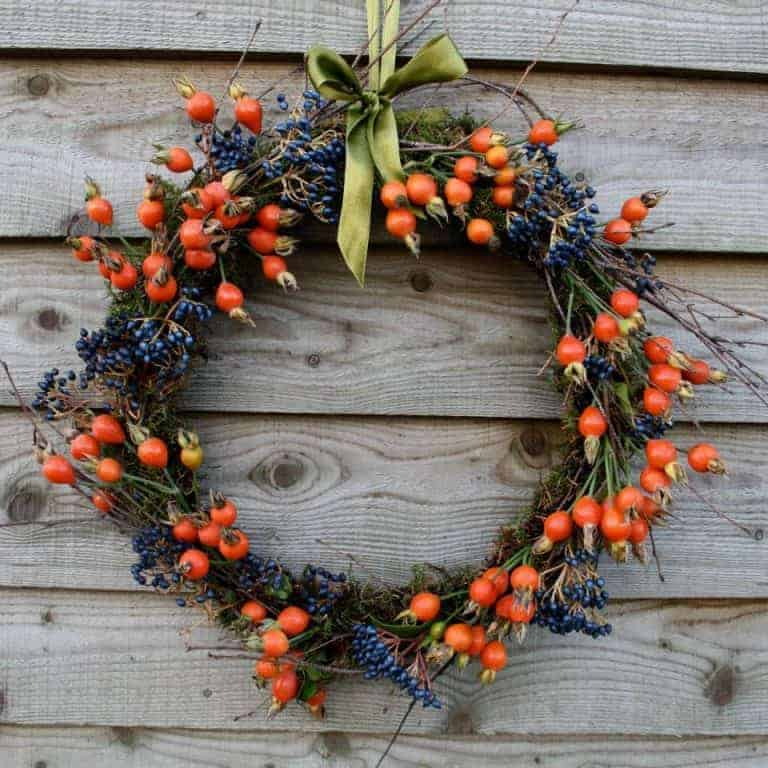 love this seasonal autumn wreath rosehips and viburnum berries. click through for more seasonal autumn flower arrangement ideas you